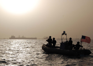 Sailors from the USS Rushmore's (LSD 47) visit, board, search and seizure team watch the sun rise over shipping and Iraqi oil platforms in the Persian Gulf on July 20, 2007.  Rushmore is currently conducting maritime operations around Iraq's Al Basrah and Khawr Al Amaya oil platforms.  DoD photo by Petty Officer 3rd Class Drew Williams, U.S. Navy.  (Released)