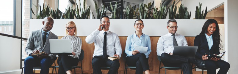 Smiling group of diverse businesspeople waiting and working together in chairs in the reception of a modern office waiting for a meeting