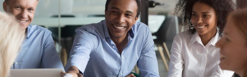 Smiling african american manager handshake greeting client at group negotiation, happy black company representative shake hand of new partner get respect make business deal at diverse team meeting